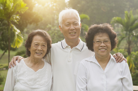 Group of healthy happy Asian seniors celebrating friendship at outdoor nature park, in morning beautiful sunlight at background. photo