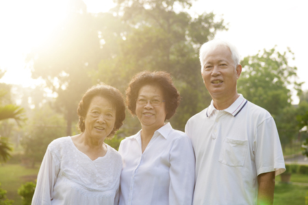 Group of healthy Asian seniors having good time at outdoor nature park, in morning beautiful sunlight at background. photo