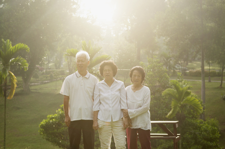 Portrait of healthy Asian seniors group enjoy retired life at outdoor nature park, in morning beautiful sunlight at background. photo
