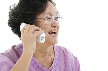 senior adult woman: Portrait of 60s Asian senior adult woman calling on telephone, isolated on white background. Stock Photo