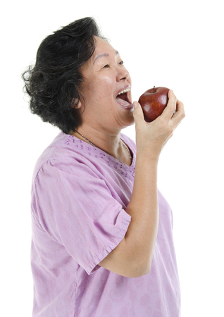 senior adult woman: Elderly healthy diet. Portrait of happy 60s Asian senior adult woman smiling and eating an apple, isolated on white background.