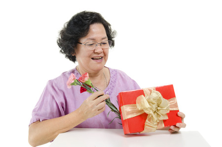 senior adult woman: Happy mothers day concept. Portrait of 60s Asian senior adult woman receiving gift box and carnation flower from her child, isolated on white background. Stock Photo