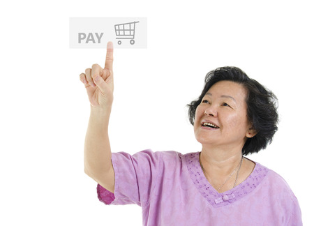 senior adult woman: Portrait of Asian senior adult woman online shopping and finger pushing at check out pay button, isolated on white background.