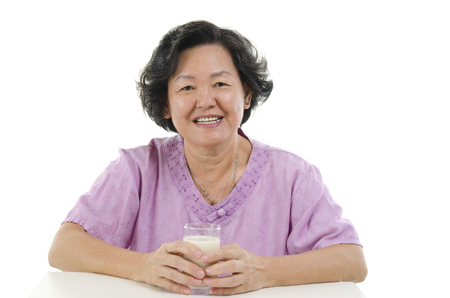 senior adult woman: Portrait of happy Asian senior adult woman hand holding a glass soy milk, isolated on white background. Stock Photo