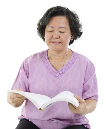 senior adult woman: Wisdom 60s Asian senior adult woman reading book, isolated on white background. Stock Photo