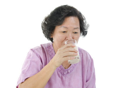 senior adult woman: Portrait of healthy 60s Asian senior adult woman drinking a glass soy milk, isolated on white background.
