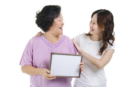 mama e hija: Portrait of Asian senior mother hand holding a white blank sign with adult daughter and smiling, isolated on white background.