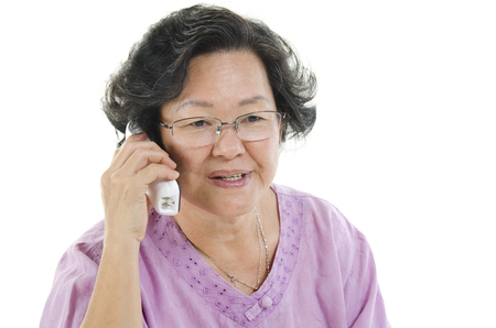 senior adult woman: Portrait of 60s Asian senior adult woman calling on phone, isolated on white background. Stock Photo