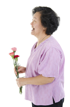 senior adult woman: Happy mothers day concept. Profile view of 60s Asian senior adult woman hand holding carnation flower gift and smiling, isolated on white background.