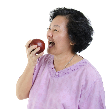senior adult woman: Elderly healthy diet. Portrait of happy 60s Asian senior adult woman eating an apple, isolated on white background. Stock Photo
