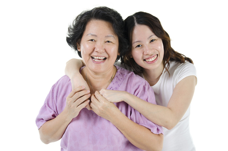 Portrait of Asian adult daughter hugging senior mother and smiling, isolated on white background.