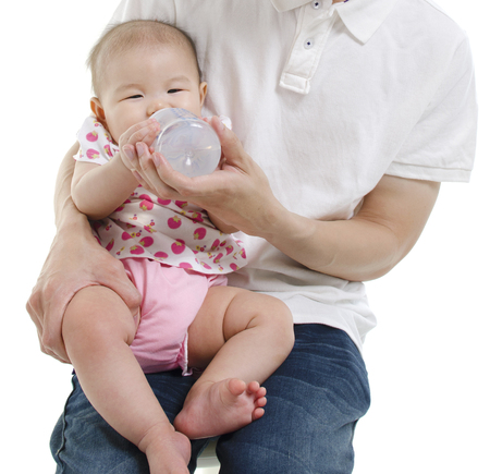 Asian father feeding baby girl drinking milk bottle, isolated on white background. photo