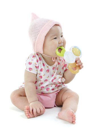 Portrait of full length beautiful Asian baby girl in pink clothes biting teether toy, isolated on white background. photo