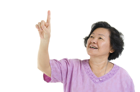 Portrait of Asian senior adult woman smiling and finger pointing at blank copy space, isolated on white background. Stock Photo