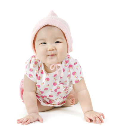 Portrait of full length happy Asian baby girl in pink clothes crawling on floor, isolated on white background. photo