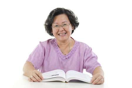 senior adult woman: Portrait of happy Asian senior adult woman reading book, isolated on white background.
