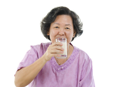 Portrait of Asian senior adult woman drinking a glass soy milk, isolated on white background. photo