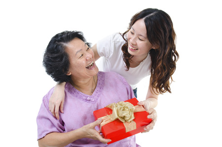 Celebrating mothers day or birthday. Portrait of Asian senior parent getting a present box from adult daughter, isolated on white background. photo