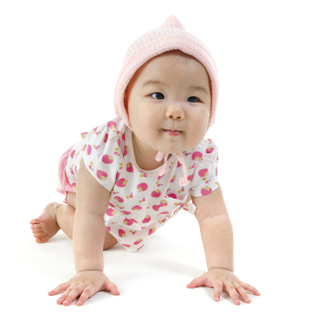 Portrait of full length Asian baby girl in pink clothes crawling on floor, isolated on white background. photo