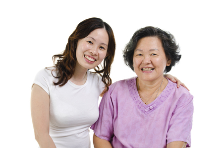 Portrait of Asian senior mother and adult daughter smiling and looking at camera, isolated on white background. photo