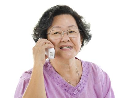 senior adult woman: Portrait of Asian senior adult woman calling on phone, isolated on white background. Stock Photo