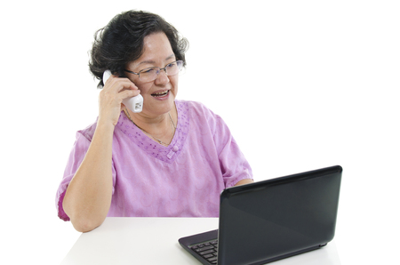 senior adult woman: Portrait of modern 60s Asian senior adult woman using laptop computer and calling on telephone, isolated on white background.