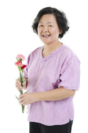 Happy mothers day concept. 60s Asian senior adult woman hand holding carnation flower gift and smiling, isolated on white background. photo