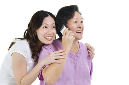 Portrait of Asian senior mother calling on phone, sharing with adult daughter and smiling, isolated on white background. photo