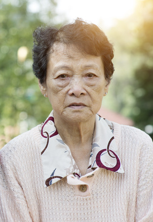 senior adult woman: Portrait of upset Asian senior adult woman at outdoor garden park in the morning. Stock Photo