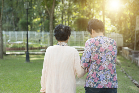Candid shot of rear view Asian senior adult women walking at outdoor park in the morning. Stock Photo