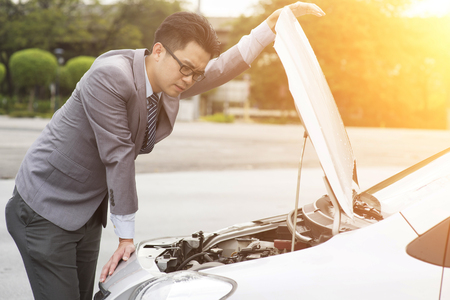 breaks: Young Asian business man looking under the hood of breakdown car.