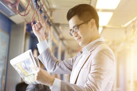 Asiatischer chinesischer Geschäftsmann, der Fahrt nimmt, im Morgen zu arbeiten und innerhalb der öffentlichen Transportmittel zu stehen und Zeitung zu lesen. Standard-Bild - 74879599