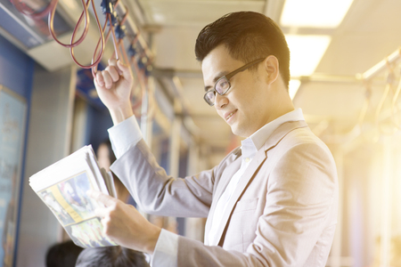 Asian Chinese businessman taking ride to work in morning, standing inside public transport and reading newspaper.