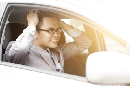 Portrait displeased angry pissed off aggressive Asian business man driving car, shouting at someone in traffic hands grabbing hair. Emotional intelligence concept. Negative human expression.