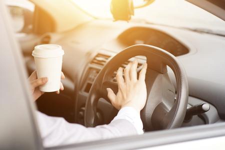cuernos: Foto del concepto de primer plano mano en dirección tocando la bocina mientras se conduce por la mañana, otra mano sostiene la taza de café.
