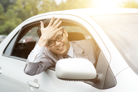banging: Portrait of pissed off  Asian business man driving car, hand banging his head in traffic jam. Negative human expression.