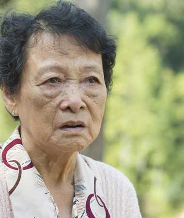 senior adult woman: Portrait of worried Asian senior adult woman at outdoor garden park in the morning.