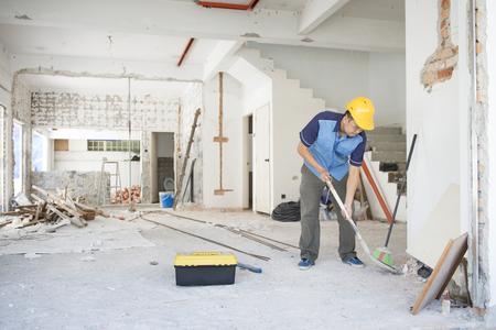 obrero trabajando: trabajador de la construcción asiático con el casco de seguridad en el lugar de trabajo, renovación de la casa.