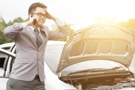 Asian business man standing by the Broken Down car and calling smart phone for help. Stock Photo