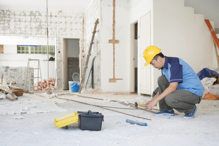 Construction worker with hardhat working at site, house renovation.