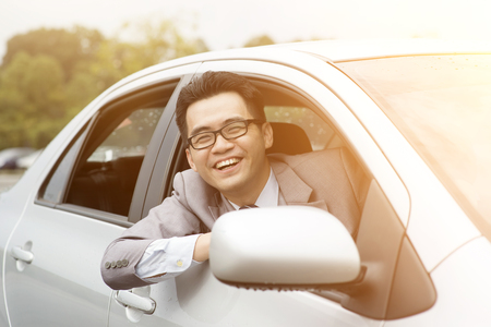 Happy driver sitting in his car and smiling. Stock Photo