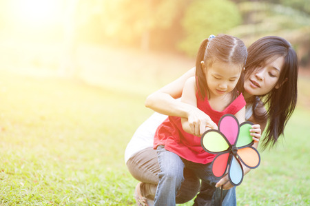 fun in the sun: Love between mother and daughter, in the park. Asian family outdoor fun, morning with sun flare.
