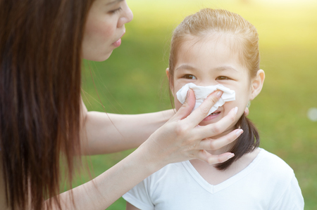 Mother helping daughter blow her nose at outside, in the park. Family outdoor lifestyle. 스톡 콘텐츠