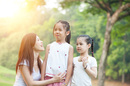 fun in the sun: Happy mother and daughters laughing together outdoors. Family outdoor fun, morning with sun flare.