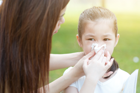 outdoor outside: Allergy. Mother and little girl blowing nose at outside, in the park. Family outdoor lifestyle.
