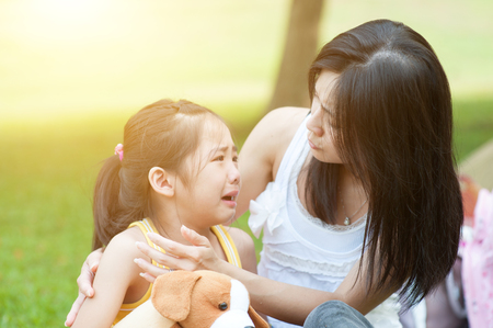 Portrait of Asian mother comforting her crying daughter in the park, Family outdoor lifestyle.