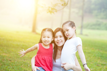 fun in the sun: Mother and daughter hugging in love playing in the park. Family outdoor fun, morning with sun flare. Stock Photo
