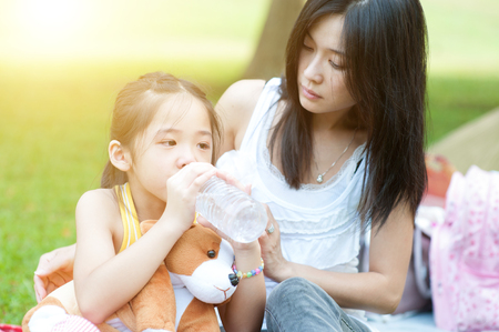 Asian mother comforting her crying child in the park, Family outdoor lifestyle. Stock Photo