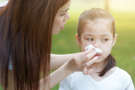 outdoor outside: Allergy. Mother helping daughter blow her nose at outside, in the park. Family outdoor lifestyle. Stock Photo