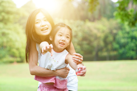 outdoor outside: Happy mother and daughter laughing together outside. Family outdoor fun, morning with sun flare. Stock Photo